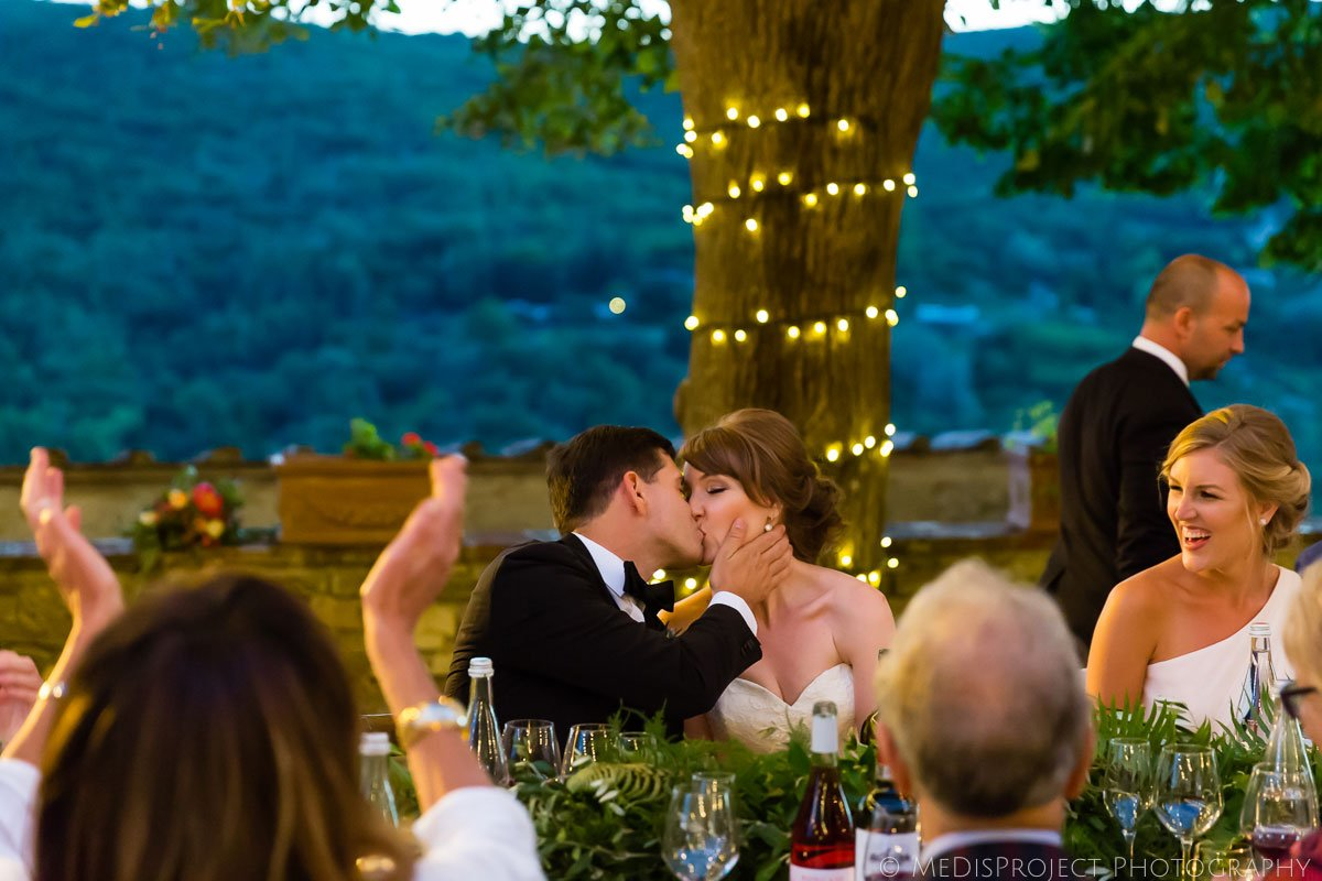 the bride and groom kissing during the wedding dinner at Meleto Castle