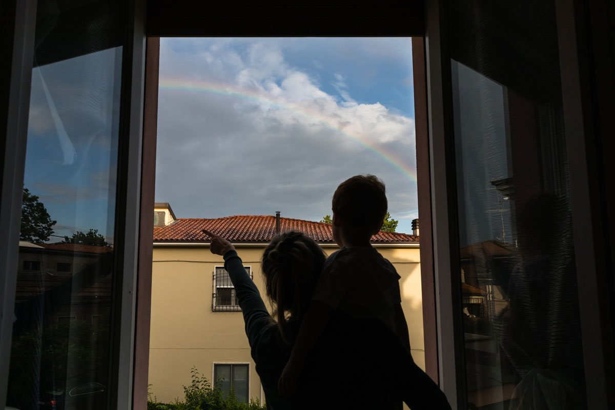 mother and son looking at the rainbow from a window