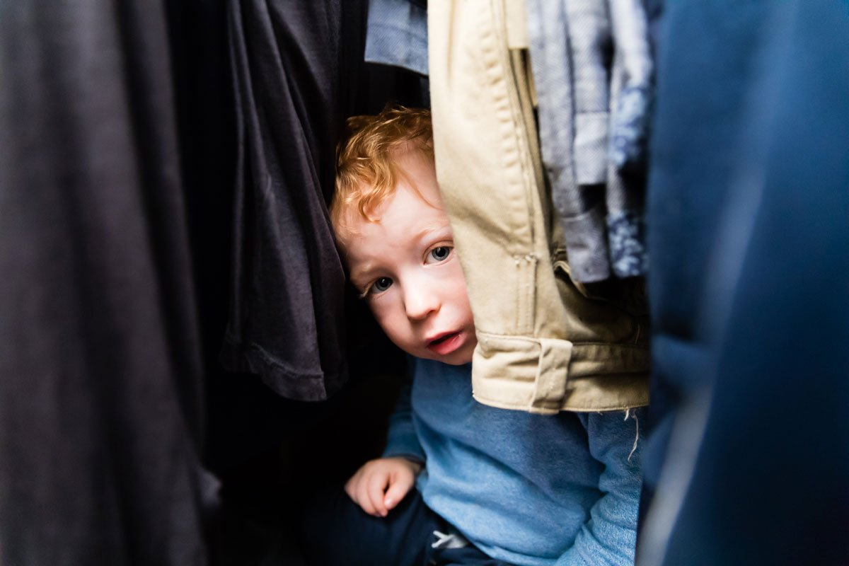 Ginger haired toddler hiding among the clothes