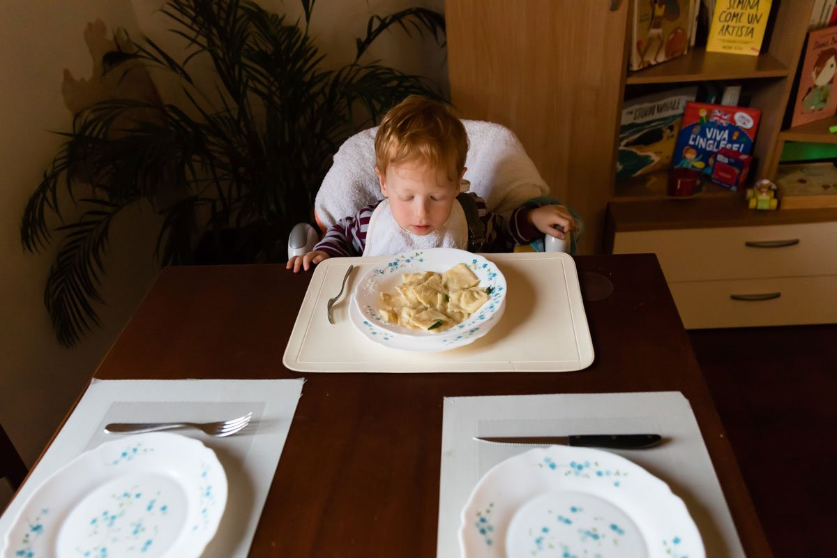 toddler eating a plate of tortelli in Italy
