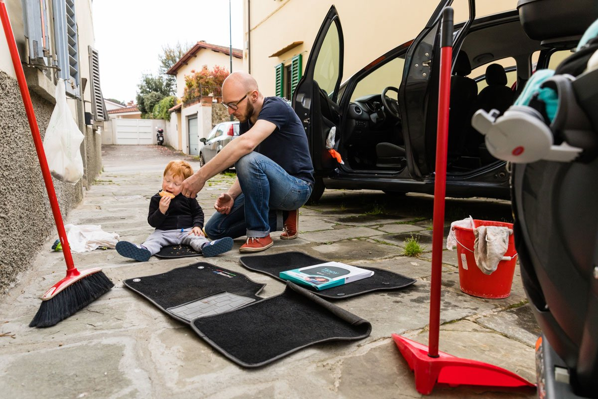 man washes his car while his toddler eats sitting on the mats