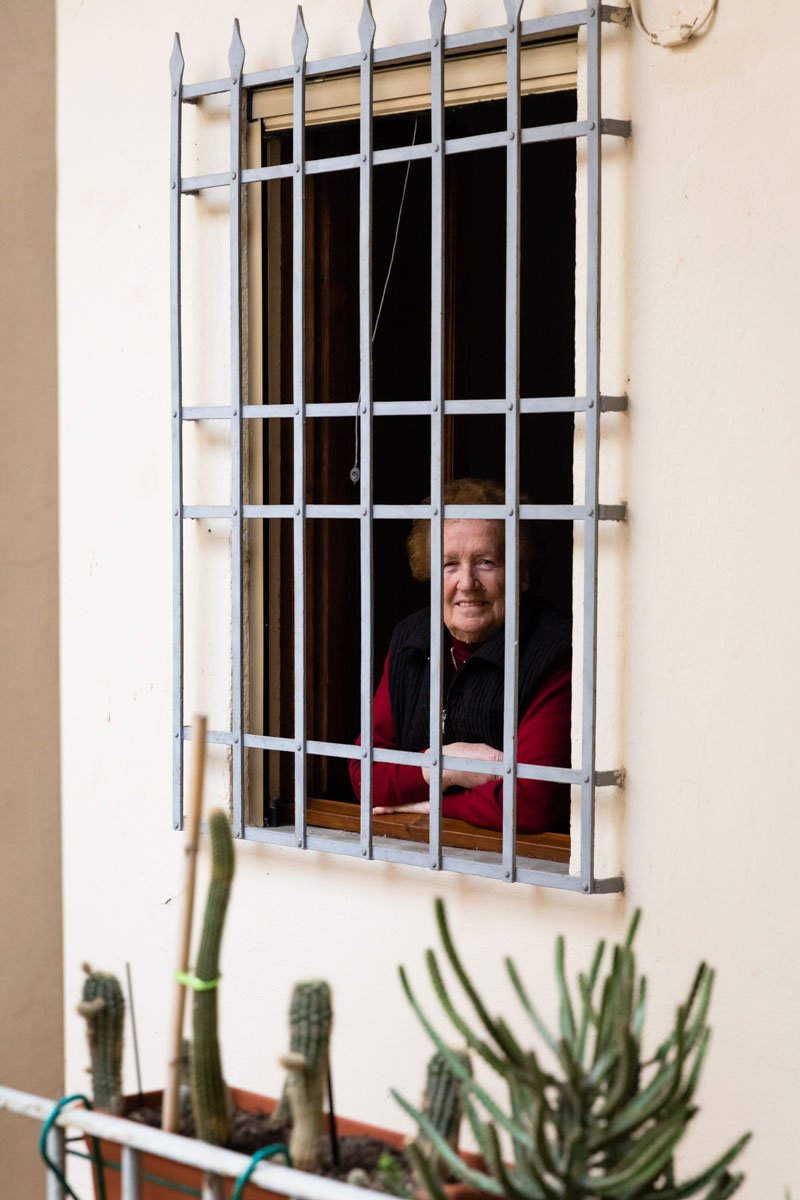 An old lady in front of her window during Covid19 lockdown in Italy