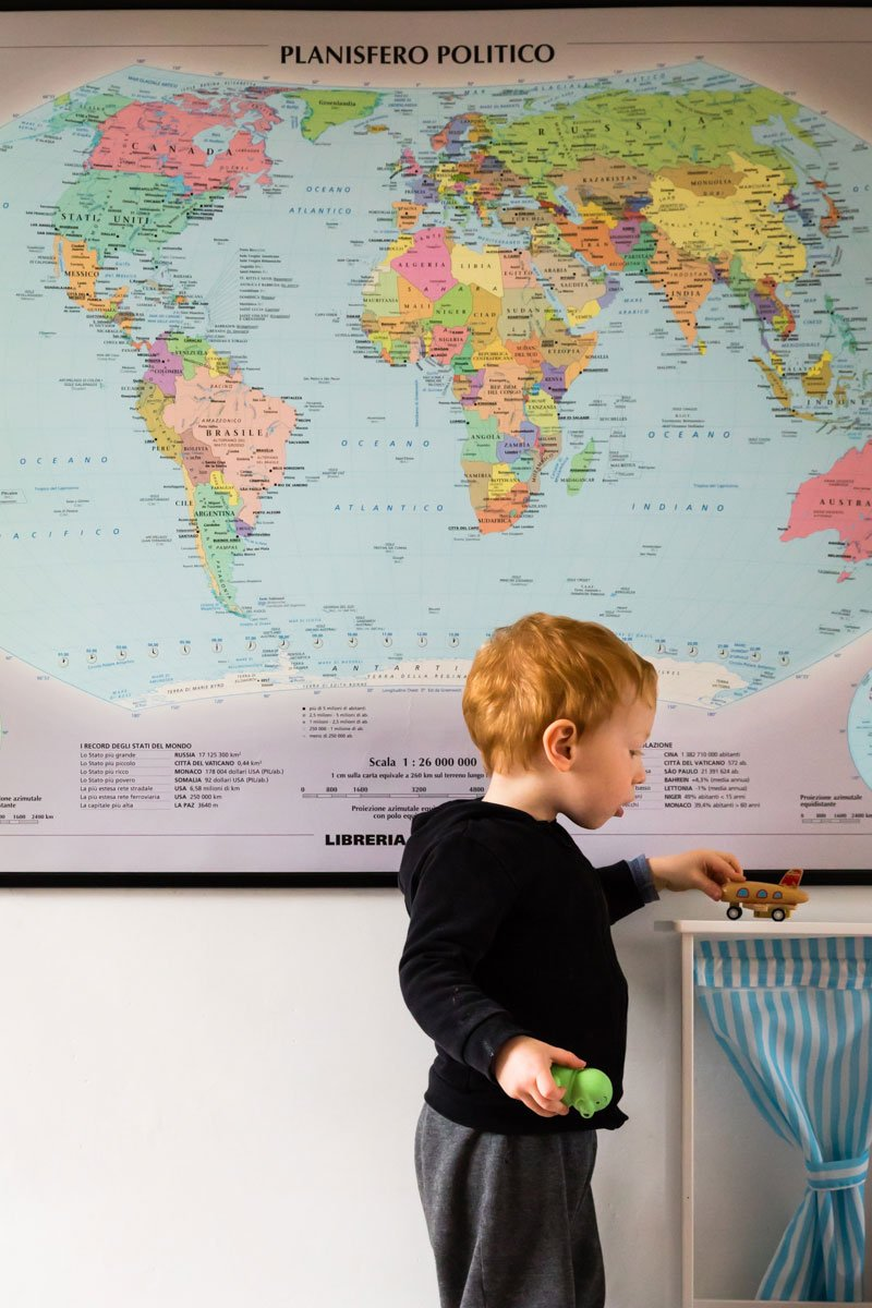 toddler playing with a toy airplane in front of a world map