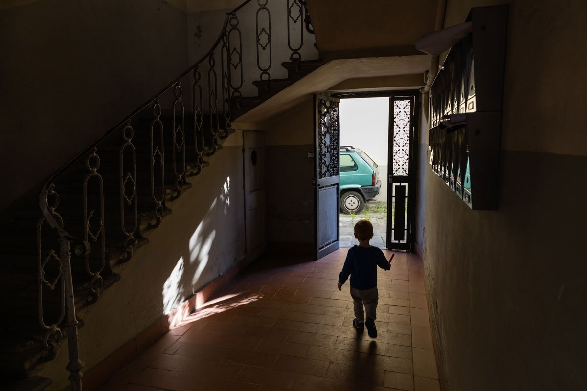 little boy running out of a building in Italy