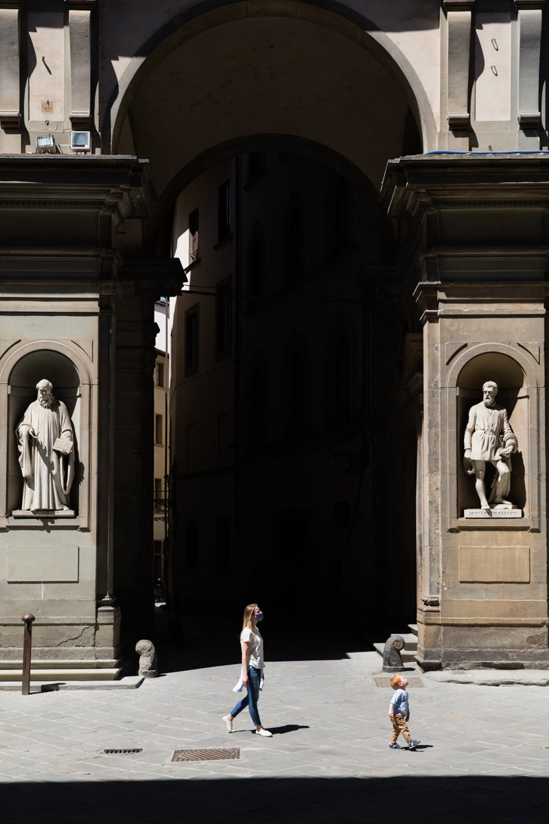 Mother and son walking the Uffizi square during coronavirus lockdown in Florence