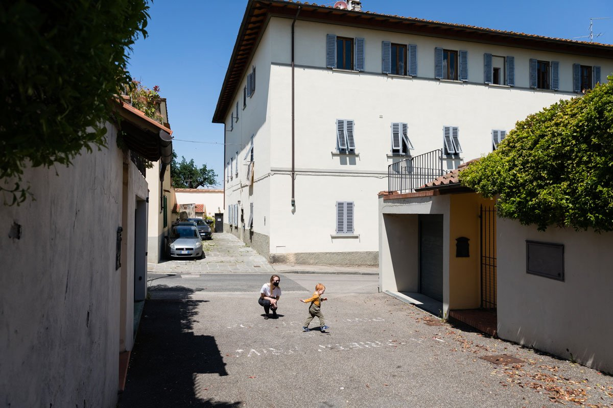 A toddler and his mother play in front of their house in Florence Italy