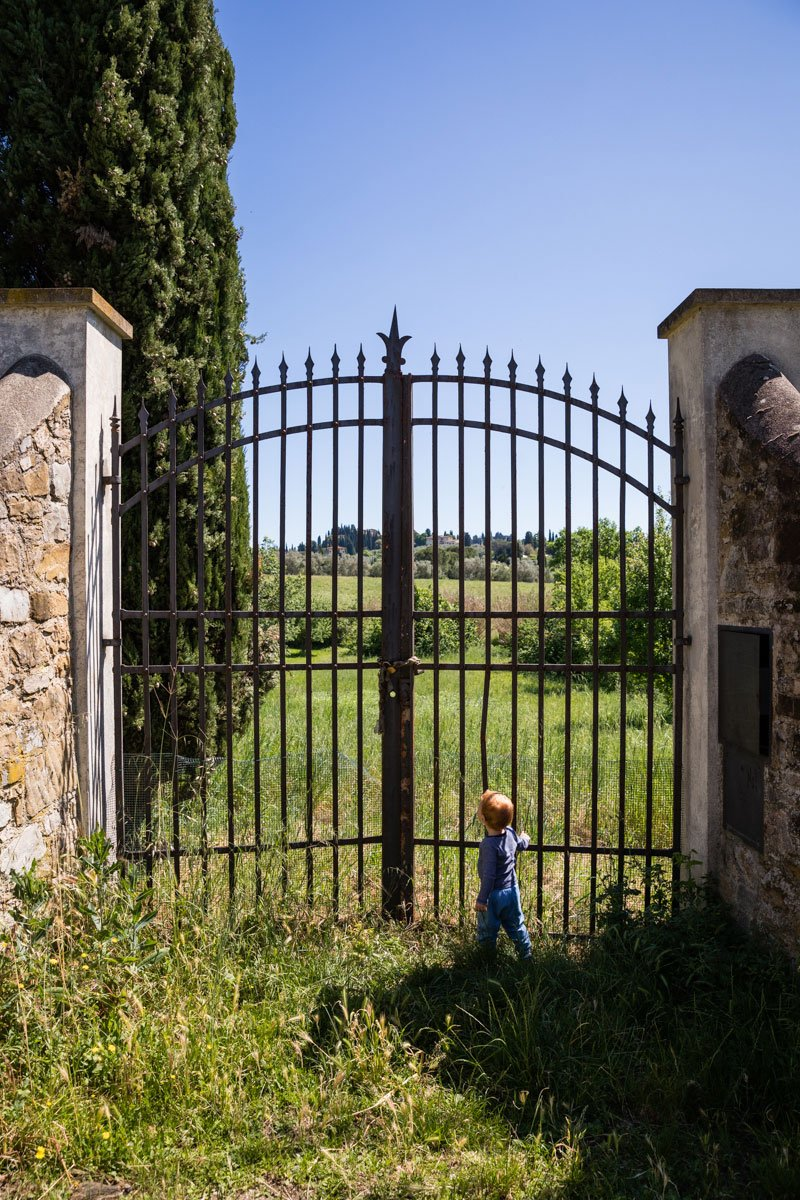 Little redhead kid in front of a gate in the fields of Tuscany