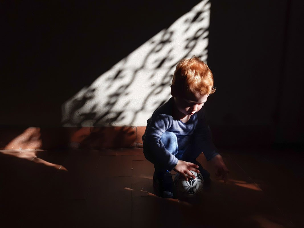 Little redhead toddler playing with a ball