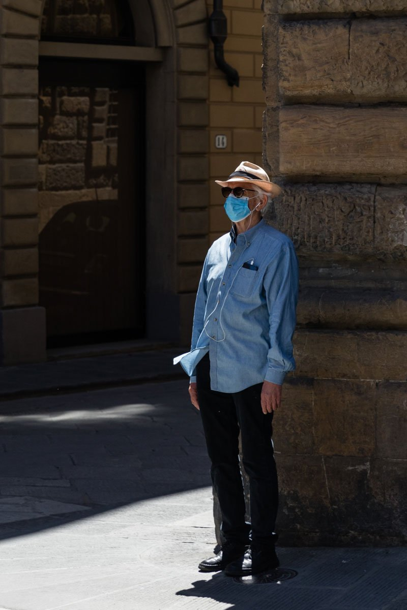 A single man wearing sunglasses and face masks in the streets of Florence