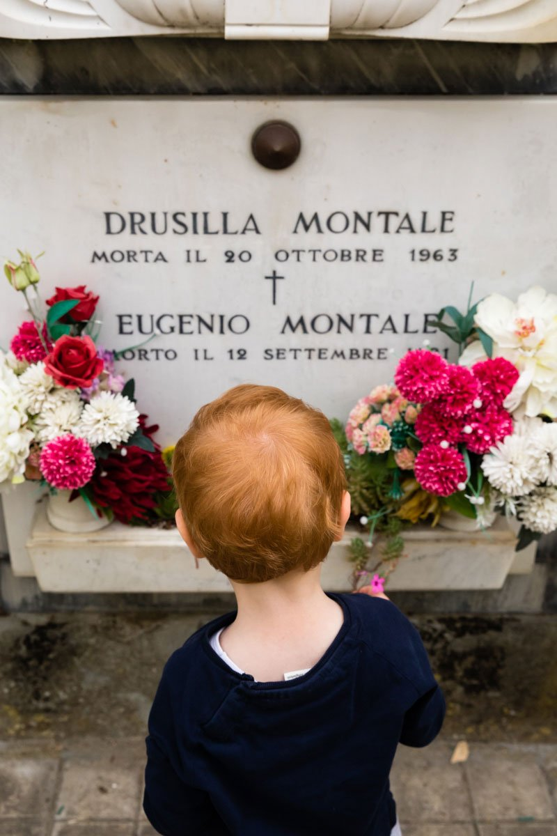 little kid in front of Eugenio Montale's grave