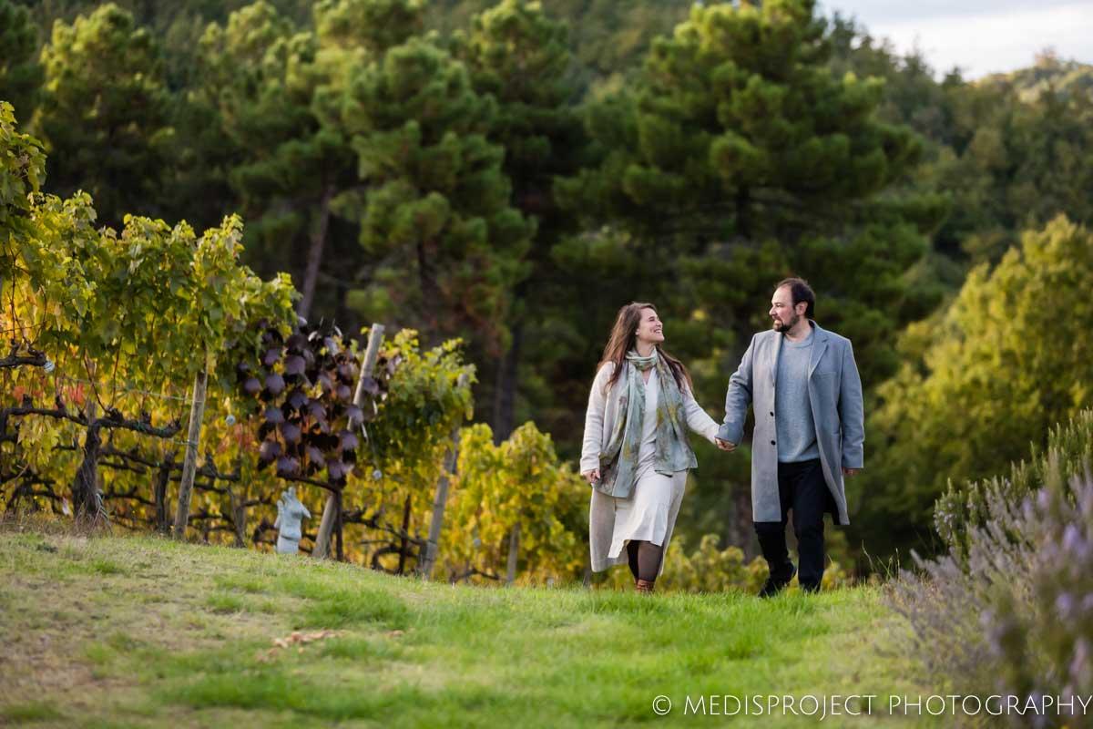 couple walking through Tuscan wineyards in autumn