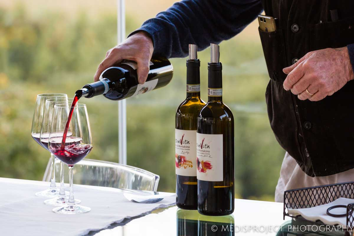 Annibale Parisi pouring red wine in glasses at NostraVita's winery