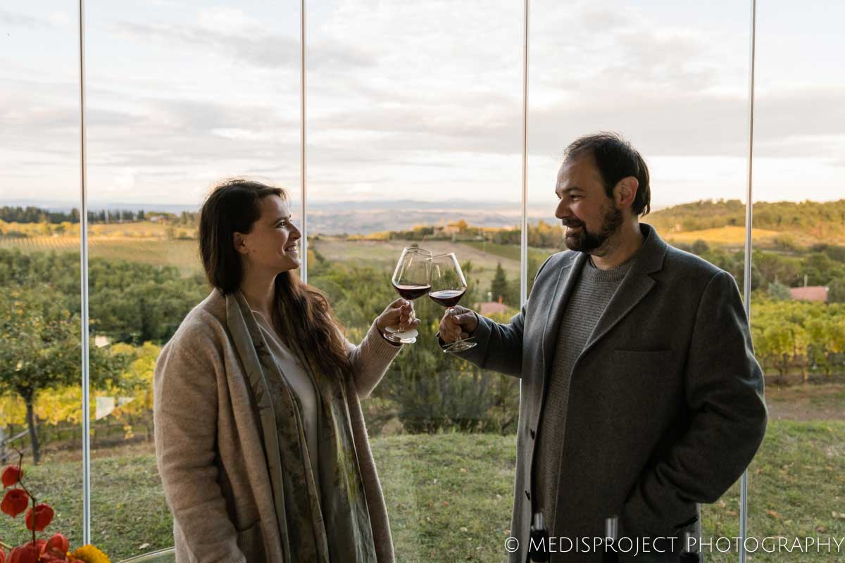couple toasting with red wine glasses at a Tuscan winery