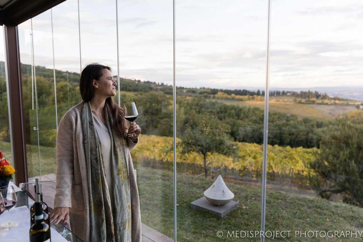 Woman tasting Brunello di Montalcino at NostraVita winery's glass gazebo