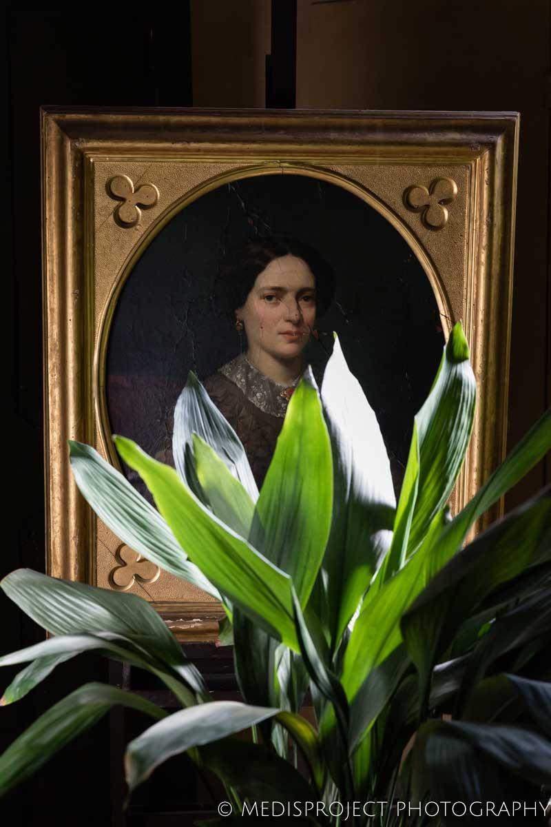 Old painting portrait peeping trough leaves