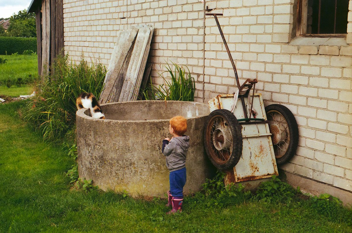 redhead kid and a cat in the backyard