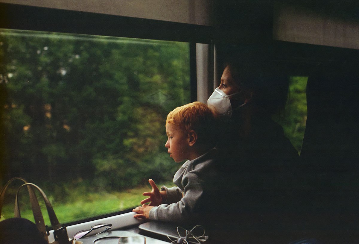 mother with face mask and son on the train in Lithuania