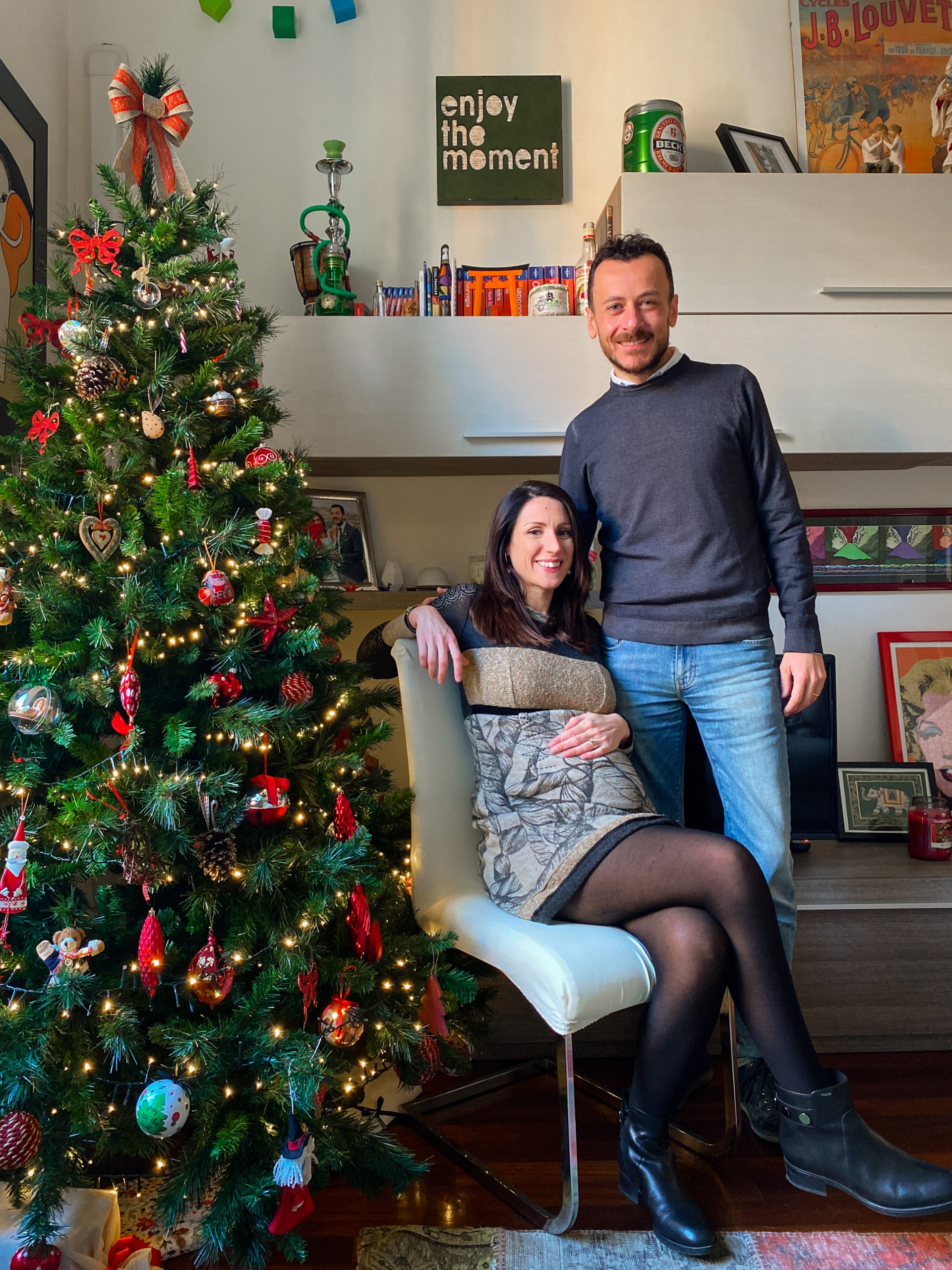pregnant woman and her husband at the christmas tree