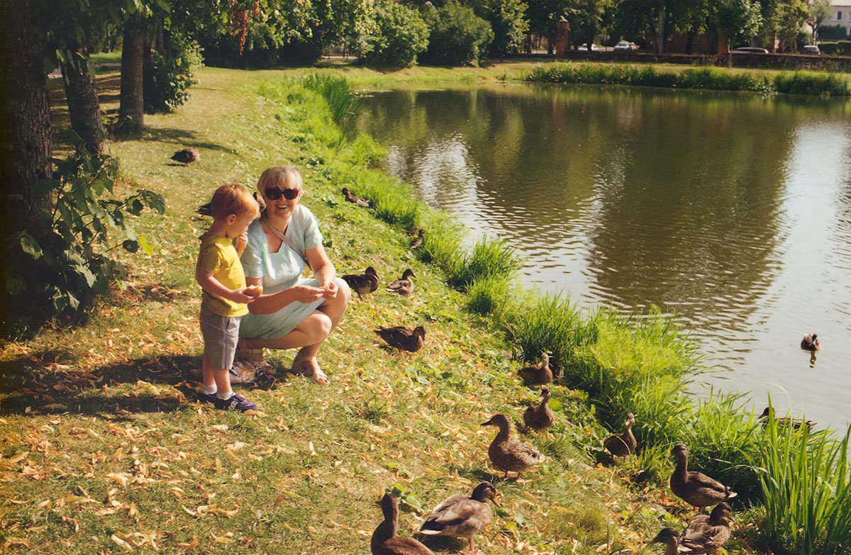 woman and little kid feeding ducks at the pond