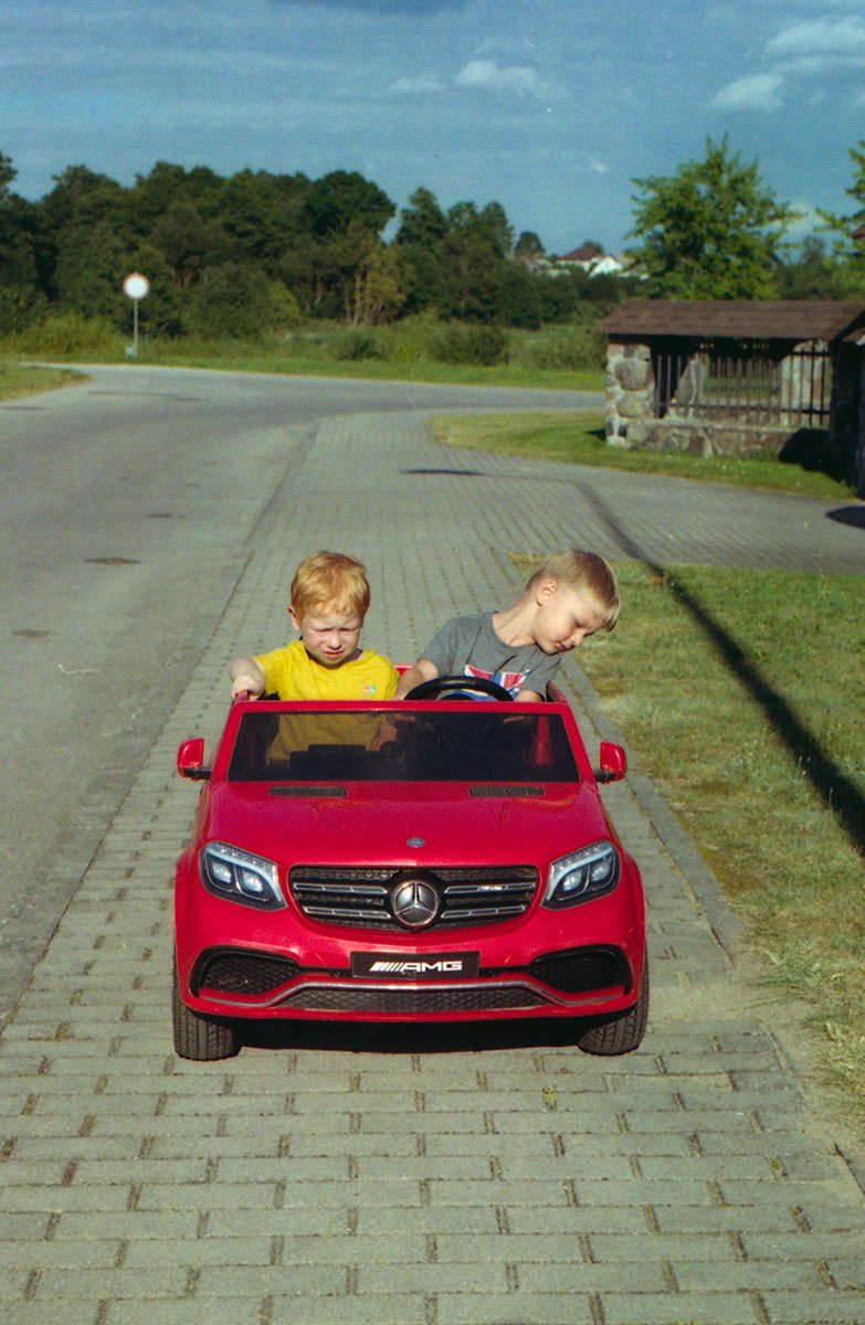 two kids on a mercedes benz kids car