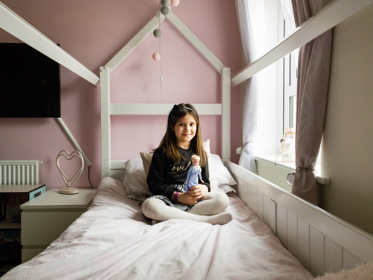online photo of a girl with a barbie in her pink room