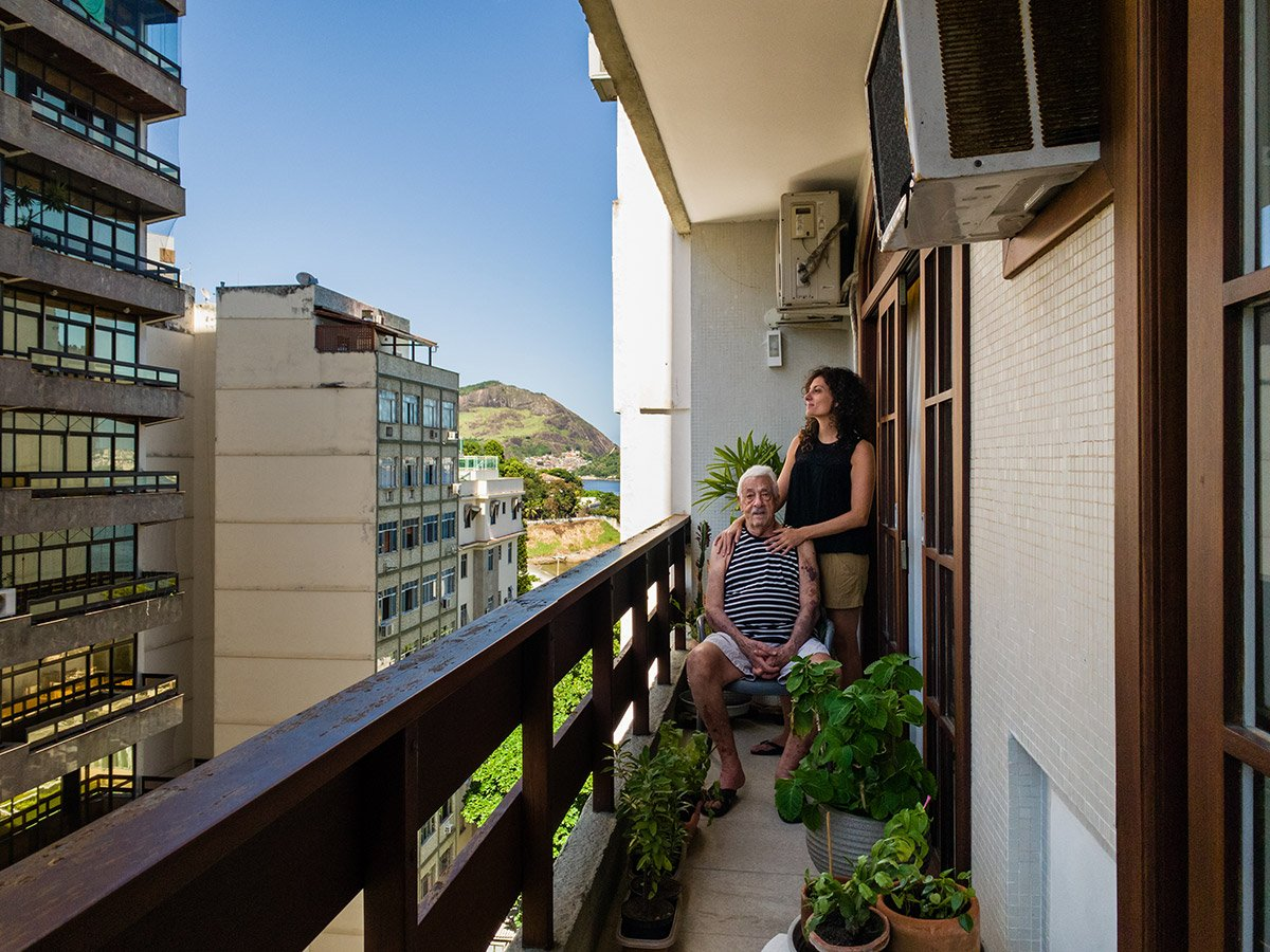 remote portrait of a woman and her grandfather on their balcony in Brazil