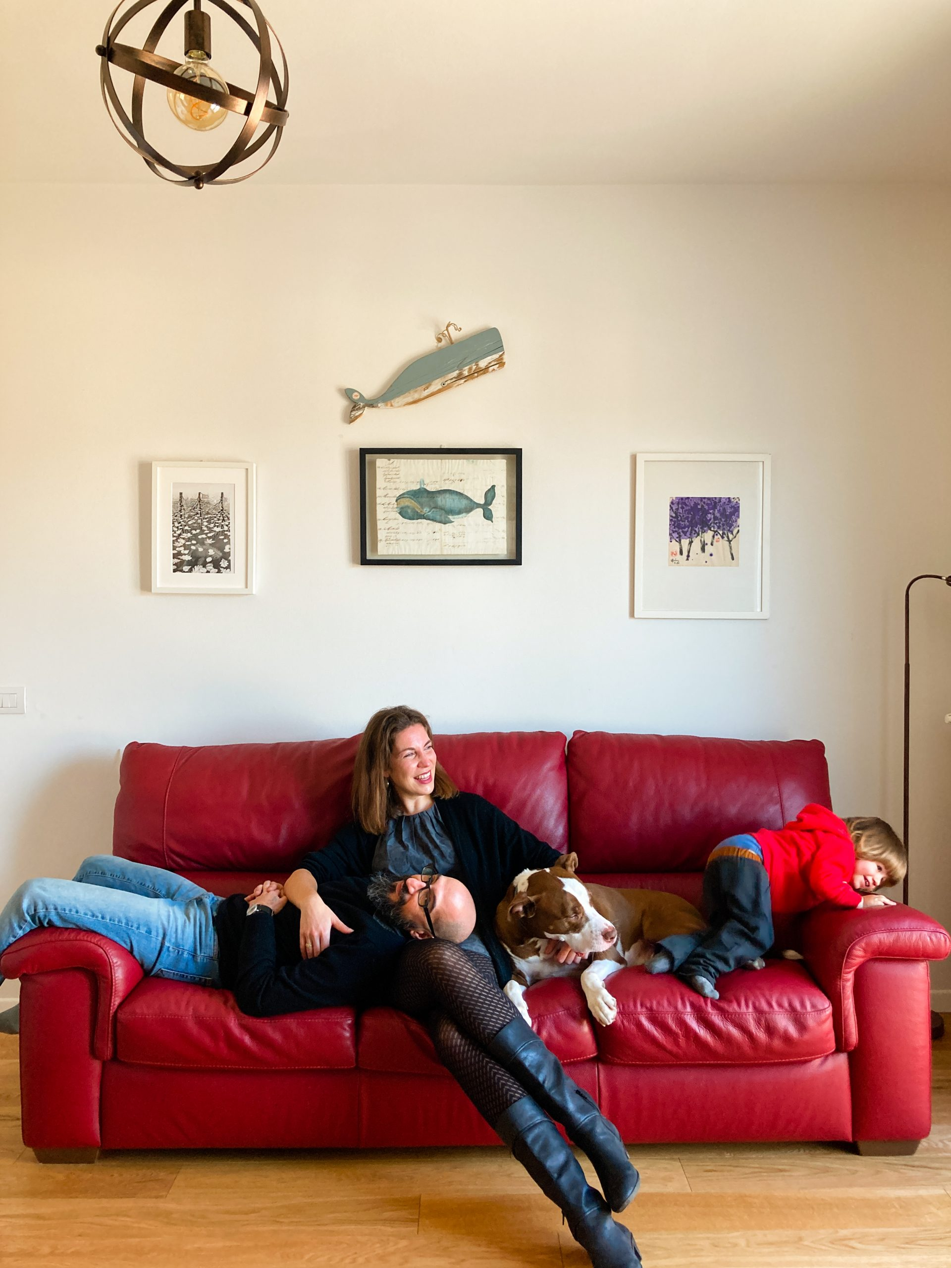 family resting on a red couch