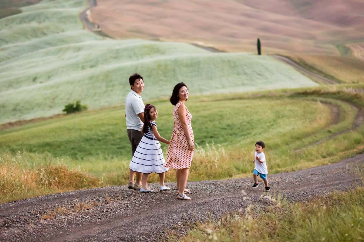 Family walking on a gravel road of Orcia Valley