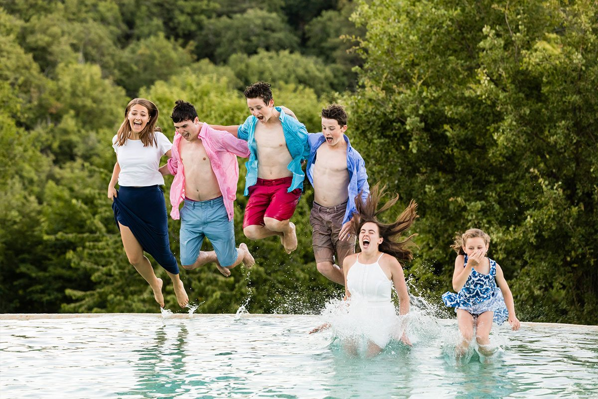 teenagers jumping in a pool in Tuscany
