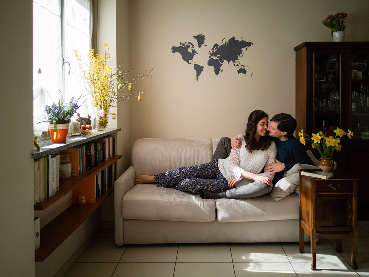 couple laying on a sofa with a map of the world