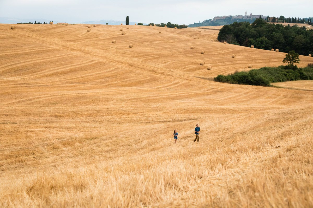 two kids in a hay bales field in Tuscany