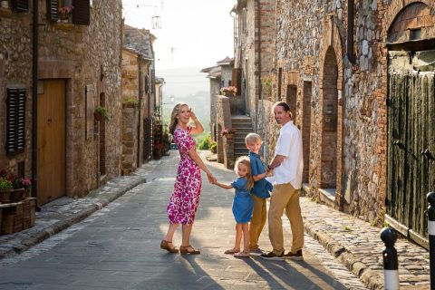 family on vacation walking in a Tuscan village